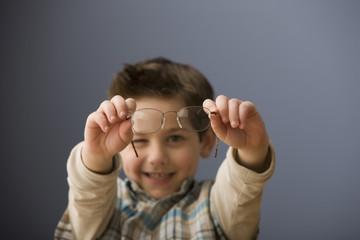 Caucasian boy holding eyeglasses