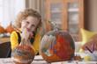 Caucasian girl painting pumpkins