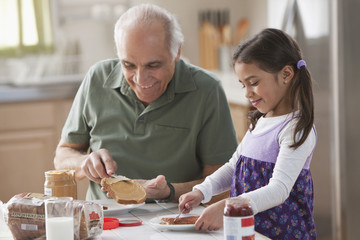 Grandfather and granddaughter making sandwiches
