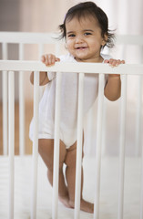 Hispanic baby girl standing in crib