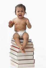 Crying Hispanic baby girl sitting on books