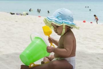 Hispanic baby girl playing in sand on beach