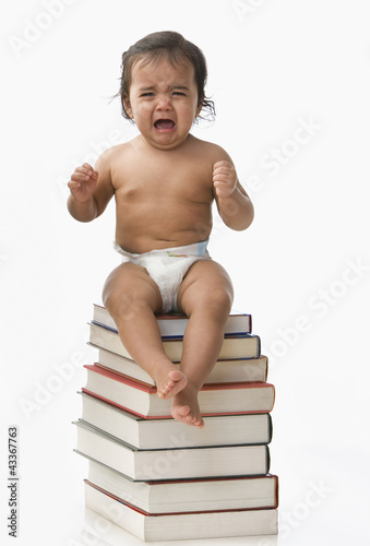 Crying Hispanic baby girl sitting on books
