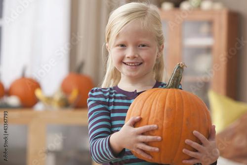 Caucasian girl holding pumpkin