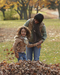 Black mother and daughter playing in autumn leaves