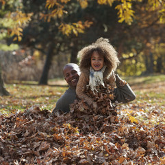 Black father and daughter playing in pile of autumn leaves