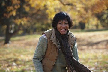 Smiling Black woman standing in autumn leaves