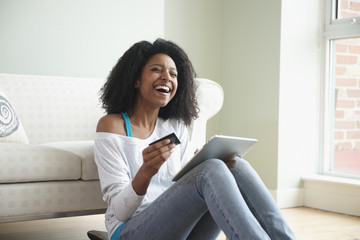 Black woman shopping online with credit card and digital tablet