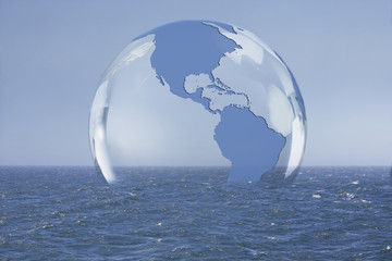 Transparent globe floating on ocean