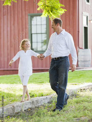 Caucasian father and daughter holding hands