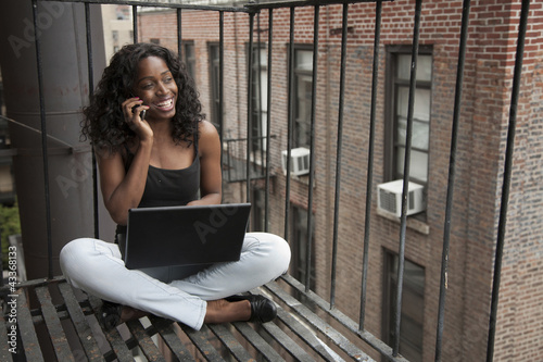 Black woman using laptop and cell phone on fire escape
