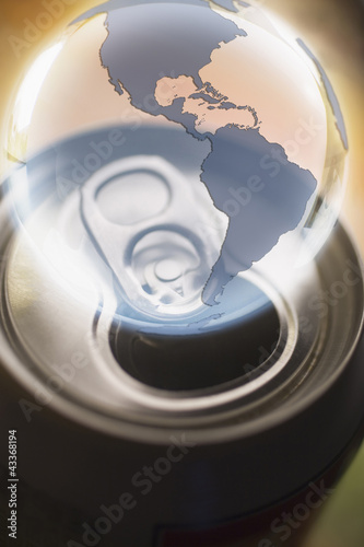 Transparent globe hovering over aluminum can