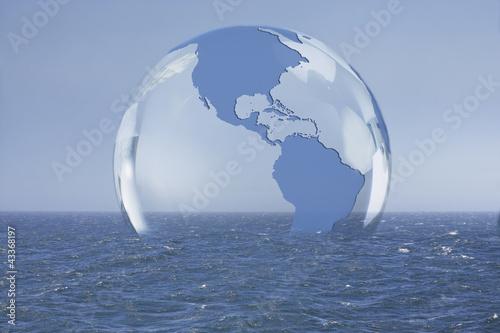 Transparent globe floating on ocean
