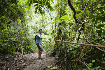 Caucasian man pulling rope in jungle