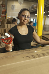 Hispanic woman taping box in warehouse