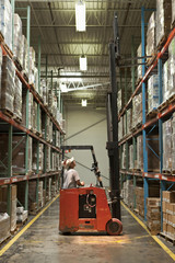 Hispanic worker operating forklift in warehouse
