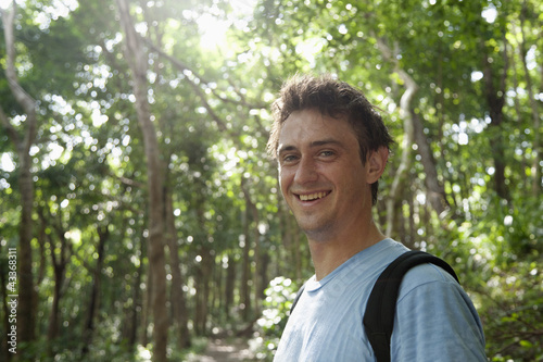 Smiling Caucasian man standing in forest