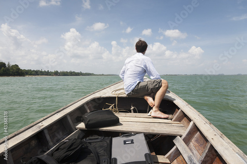 Caucasian businessman riding in boat