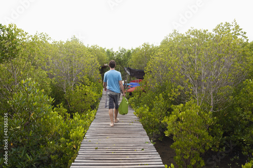 Caucasian man walking on wooden boardwalk