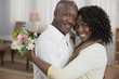 African American man bringing wife flowers