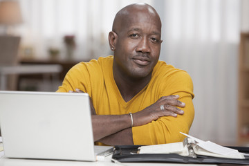 Serious African American man sitting with laptop