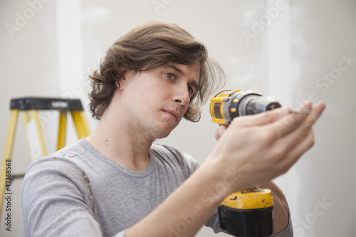 Caucasian man using drill