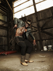 Trendy African American man dancing in warehouse