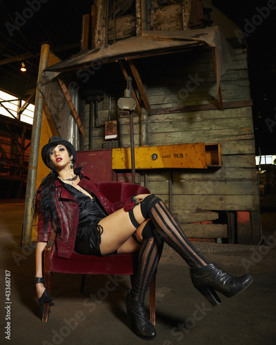 Trendy mixed race woman sitting in warehouse