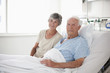 Wife sitting with husband in hospital bed
