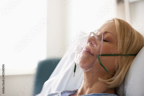 Caucasian patient laying in hospital bed in oxygen mask
