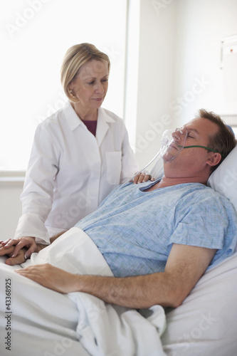 Doctor comforting patient in hospital bed