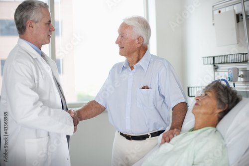 Doctor talking to patient's husband in hospital room