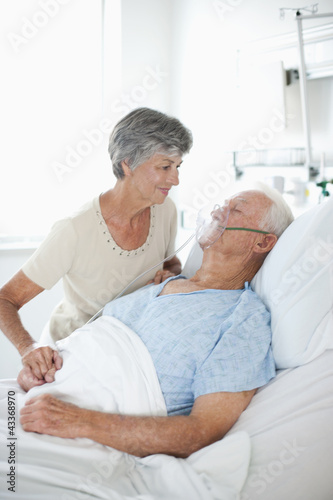 Wife watching husband with oxygen mask in hospital bed