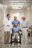 Doctor and nurse walking with patient in wheelchair in hospital