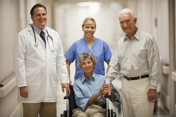 Doctor and nurse with patient in wheelchair in hospital