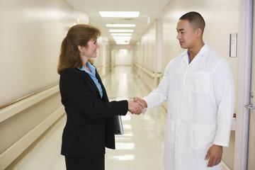 Doctor shaking businesswoman's hand in hospital corridor