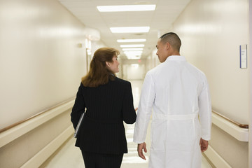 Doctor walking with businesswoman in hospital corridor