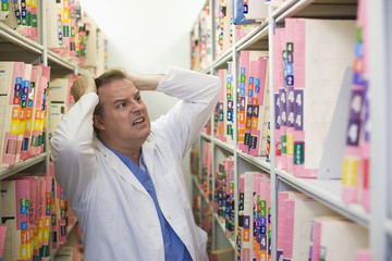 Frustrated Caucasian doctor searching for medical record in file room