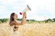 Woman with megaphone in the wheat field