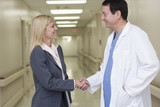 Businesswoman shaking hands with doctor in hospital corridor