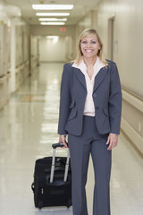 Caucasian businesswoman pulling suitcase in hospital corridor