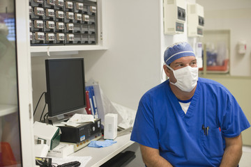 Doctor wearing surgical mask sitting in hospital