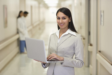 Indian businesswoman standing in hospital corridor holding laptop