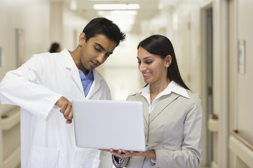 Businesswoman showing laptop to doctor in hospital