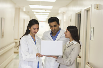 Businesswoman showing laptop to doctors in hospital corridor