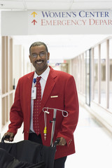 African American hospital worker pushing wheelchair in corridor