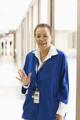 Hospital worker waving in corridor