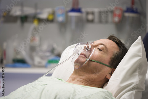 Patient laying in hospital bed with oxygen mask