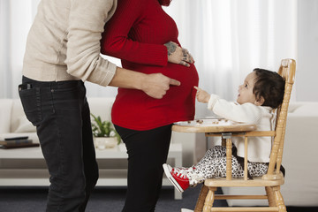 Hispanic baby pointing to mother's pregnant stomach