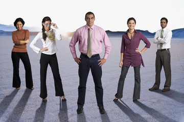 Diverse business people standing together in desert